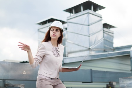 Blured roof on background, attractive redhead caucasian businesslady in beige suit, brown trousers and white helmet sit on the roof and hold  laptop, serious, point at left