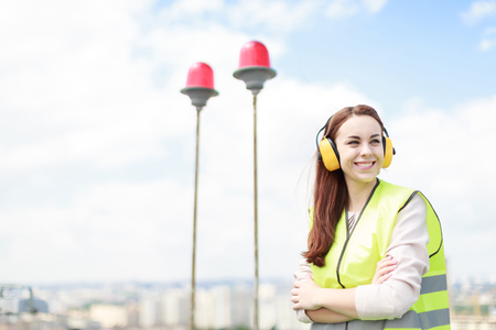 Blured sky and red signal lights on background, young pretty brunette caucasian woman in green west and yellow earmuffs stand on roof, look right