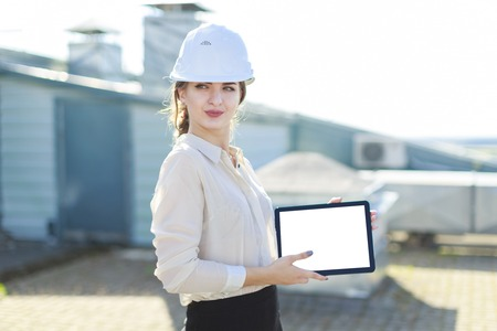 Blured roof on background, attractive brunette caucasian businesslady in white blouse, watch, white helmet and black skirt stand on the roof and show empty tablet, look at camera Stock Photo