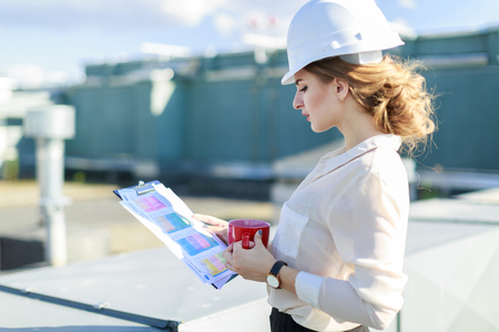 Blured roof on background, pretty brunette caucasian businesslady in white blouse, watch, white helmet and black skirt stand on the roof and hold tablet and red cup, look in tablet