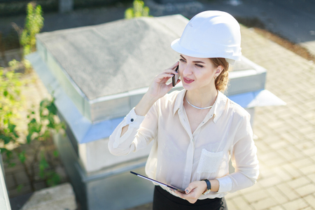 Blured roof on background, pretty brunette caucasian businesslady in white blouse, watch, white helmet and black skirt stand on the roof, hold tablet and talk a phone, from top, smiling Stock Photo