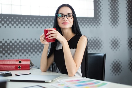 Office on background, pretty, young brunette caucasian businesslady in black dress and glasses sit at the table and hold red cup with coffe, office stuff and laptop on the desk