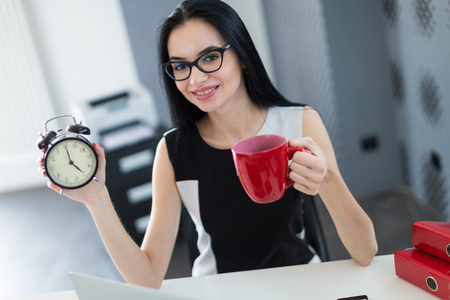 Office on background, beautiful young brunette caucasian businesswoman in black dress and glasses sit at the table, work with laptop, hold red cup and alarm clock , look at camera stuff on the desk