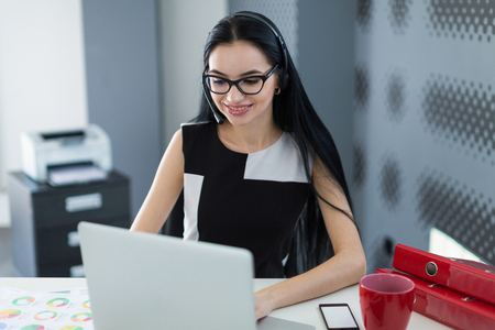 Office on background, young atractive brunette caucasian businesslady in black dress, glasses and headset sit at the table and work with laptop