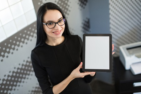 Office on background, beautiful young brunette caucasian businesswoman in black dress and glasses hold red paper folder, show empty tablet, smiling