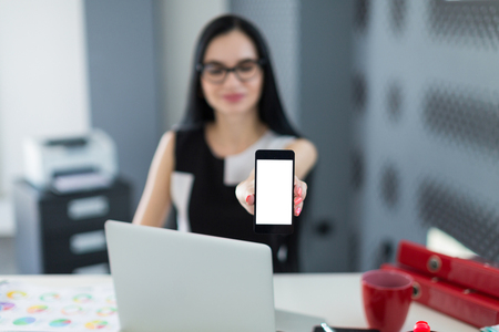 Office on background, beautiful young brunette caucasian businesswoman in black dress and glasses sit at the table, work with laptop, show phone, blured girl, focus on phone  office stuff on the desk
