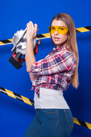 Isolated on blue, attractive sexy brunette caucasian builder girl in chechered shirt, yellow build goggles, snickers and blue jeans stand with circular saw in hands Black-yellow tape