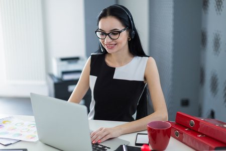 Office on background, young atractive brunette caucasian businesslady in black dress, glasses and headset sit at the table and work with laptop, smiling
