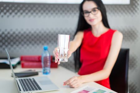 Office on background, pretty, young brunette caucasian businesslady in red dress and glasses sit at the table and work with laptop, water bottle on the desk, show glass, focus on glass, look at camera