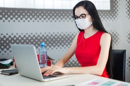 Office on background, pretty, young brunette caucasian businesslady in red dress, respirator and glasses sit at the table and work with laptop, water bottle on the table 스톡 콘텐츠