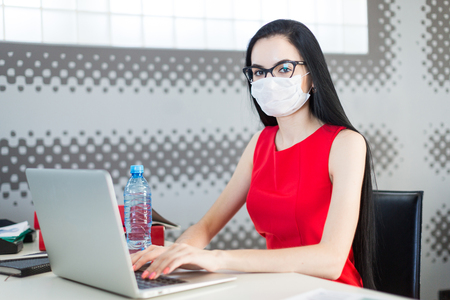 Office on background, pretty, young brunette caucasian businesslady in red dress, respirator and glasses sit at the table and work with laptop, water bottle on the table, look at camera Standard-Bild