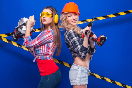 Isolated on blue, attractive sexy caucasian builder girls in chechered shirts, first in shorts hold drill, second in jeans hold cercular saw, both look at camera