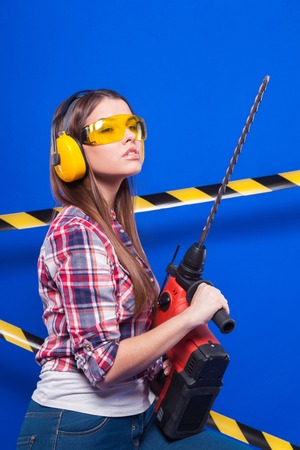 Isolated on blue, smiling sexy brunette caucasian worker girl in chechered shirt, yellow build goggles, yellow earmuffs, snickers and blue jeans stand with drill, look at camera Black-yellow tape