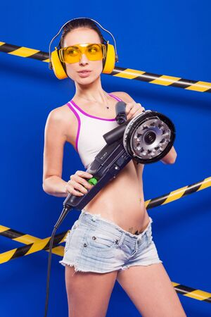 Isolated on blue, beautiful brunette caucasian builder girl in denim shorts, white snickers, earmuffs, glasses and white top shirt hold electro saw, look up Stock Photo