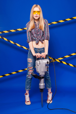 Isolated on blue, beauty blonde caucasian builder girl in chechered shirt, jeans and yellow builder glasses hold long grey puncher, look at camera