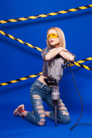 Isolated on blue, beauty blonde caucasian builder girl in chechered shirt, jeans and yellow builder glasses hold long grey puncher, stand on knees