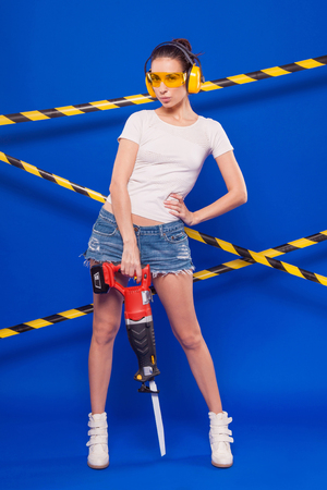 Isolated on blue, pretty brunette caucasian builder girl in denim shorts, white snickers, yellow earmuffs, glasses and white top shirt hold red electro saw, look at camera, hand on waist