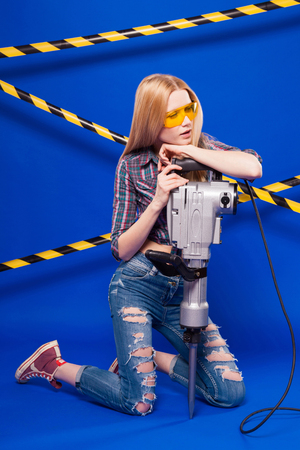 Isolated on blue, beauty blonde caucasian builder girl in chechered shirt, jeans and yellow builder glasses hold long grey puncher, stand on knees, relies on the puncher Stock Photo