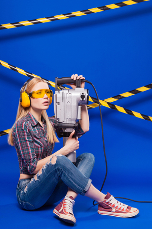 Isolated on blue, beauty blonde caucasian builder girl in chechered shirt, jeans and yellow builder glasses hold long grey puncher, sit crossed legs, loo at left Stock Photo