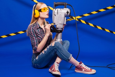 Widescreen picture, isolated on blue, beauty blonde caucasian builder girl in chechered shirt, jeans and yellow builder glasses hold long grey puncher, sit crossed legs Stock Photo