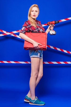 Isolated on blue, attractive blonde caucasian builder girl in red chechered shirt, jean shorts and snickers hold screwdriver and red toolbox, look at camera