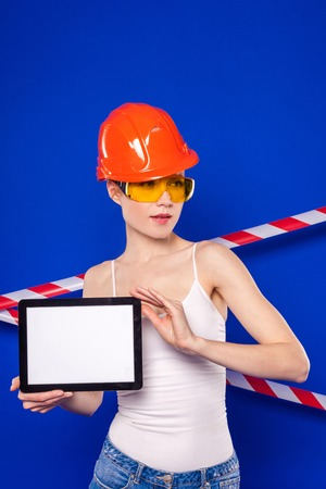 Isolated on blue, attractive blonde caucasian builder woman in white shirt, builder belt, yellow builder glasses, orange building helmet and jean shorts shows empty tablet