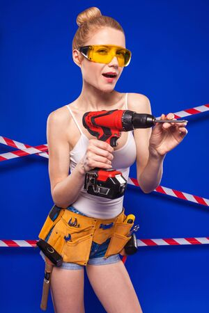 Isolated on blue, young blonde caucasian builder girl in white shirt, builder belt, yellow builder glasses, jean shorts and snickers hold red screwdriver, frisky look Stock Photo