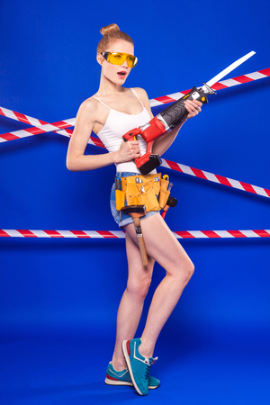 Isolated on blue, young blonde caucasian builder girl in white shirt, builder belt, yellow builder glasses, jean shorts and snickers hold red electrosaw with long blade Stock Photo