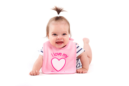 Isolated on white, cute baby girl in pink bib and striped shirt, cheerful, happy, with ponytail Stock Photo