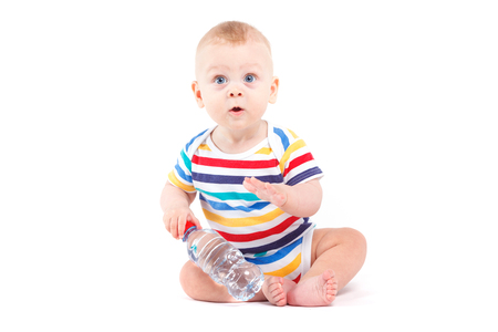 only boys: Isolated on white, cute pretty caucasian baby boy in striped colorful shirt sit and hold water bottle, amazed
