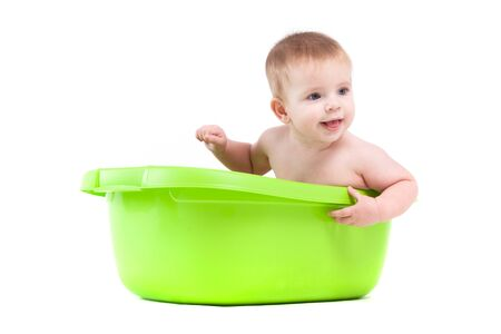 isolated on white, cute attractive caucasian baby boy take bath in green tub