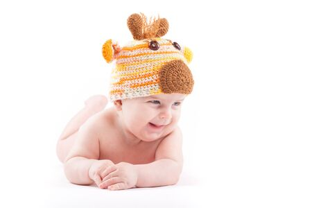 isolated on white, cute happy caucasian baby boy in white diaper and deer hat lies, laugh Stock Photo