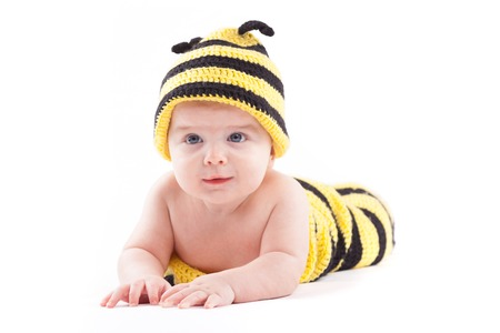 isolated on white, cute happy caucasian baby boy in diaper and bee costume lies, serious