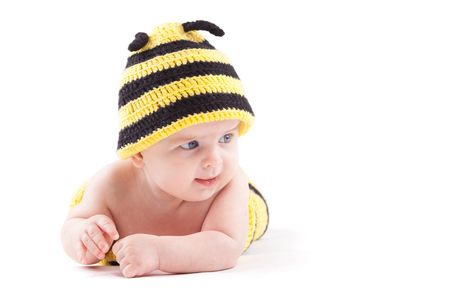 isolated on white, cute nice caucasian baby boy, in bee costume lies on tummy, relies on hands