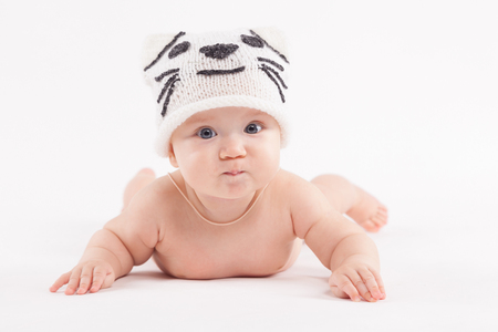 isolated on white, happy baby caucasian boy in diaper and white cat hat lies