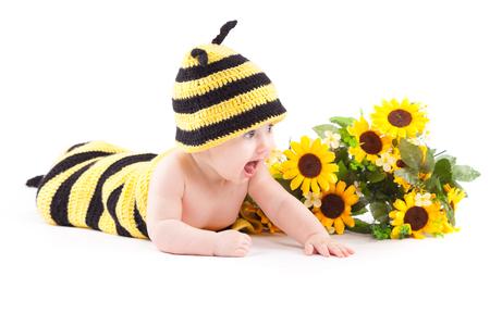 isolated on white, cheerful baby caucasian girl in bee costume near sunflowers