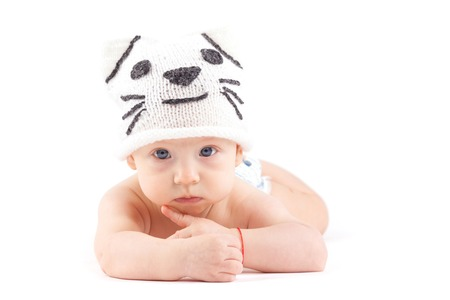 isolated on white, cute nice caucasian baby boy, in white diaper and white cat hat lies on tummy, look at camera, hand on mouth, offended