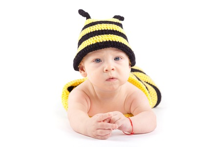 isolated on white, cute nice caucasian baby boy, in bee costume lies on tummy, look at camera, serious Stock Photo