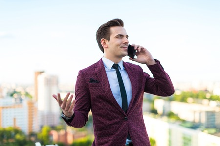 Attractive young brunette caucasian businessman in red business suit, white shirt, black tie, black trousers and costly watch stand on the roof and talk on the black cellphone blured city on background Stock Photo