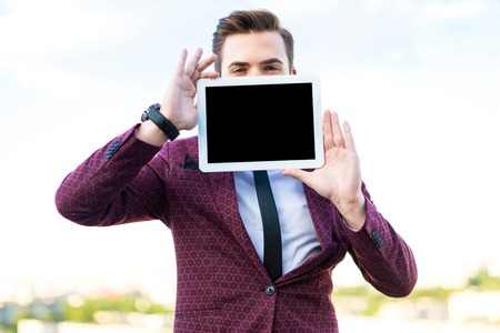 Attractive serious brunette caucasian businessman in red business suit, white shirt, black tie, black trousers and costly watch stand on the roof with empty tablet in hands in front of his face, look out from tablet, look at camera blured city on background