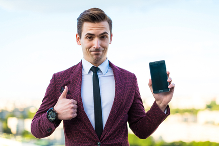 Attractive young brunette caucasian businessman in red business suit, white shirt, black tie, black trousers and costly watch stand on the roof and hold black cellphone, show phone, look at camera, show thumbs up blured city on background Stock Photo