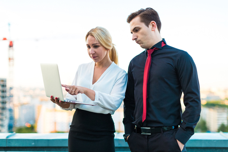 Couple of businessmen, young good looking brunette caucasian man in dark suit, red tie  and black shirt, and attractive blonde woman in white blouse and black skirt stand on the roof and hold one laptop, mans hands in pockets blured city on background