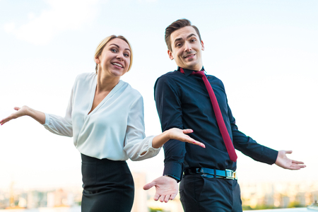 vómito: Couple of caucasian businessmen, young attractive brunette man in dark suit, red tie  and black shirt, and pretty blonde woman in white blouse and black skirt stand on the roof back to back, both with crossed hands, both threw up their hands blured city on background