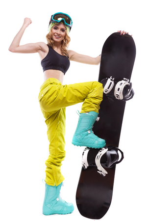 vertical picture, isolated on white, attractive caucasian pretty young woman in ski goggles, yellow trousers and black short tank top hold black snowboard, one hand up