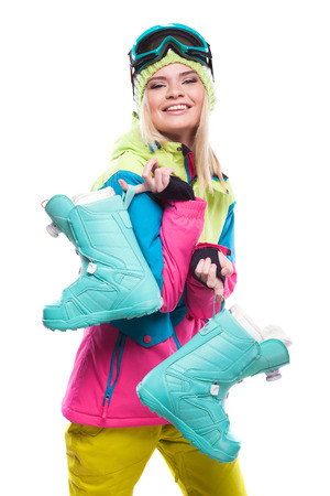 vertical picture, isolated on white, blonde pretty young caucasian woman in colorful ski outfit and blue snow goggles, hold blue snow boots, look at camera, boots on front Stockfoto
