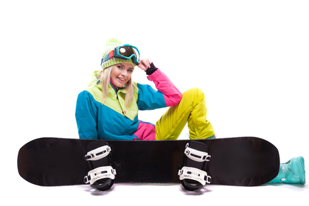 vertical picture, isolated on white, blonde pretty young caucasian woman in colorful ski outfit, yellow trousers and blue snow glasses sitting cross-legged near snowboard, hand on head, snowboard at front, look at camera 版權商用圖片