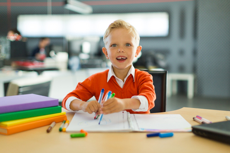 Cute blonde caucasian kid sit at the table with colorful folders and draws with pen, hold colorful handles, amazed, look at camera Office workers at background, blurred back, focus on lad 免版税图像