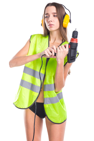 young sexy woman in green builder outfit, yellow earmuffs and black bikini, hold screwdriver with both hands, sad 免版税图像