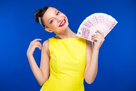 girl holding a lot of money in a yellow dress in retro style