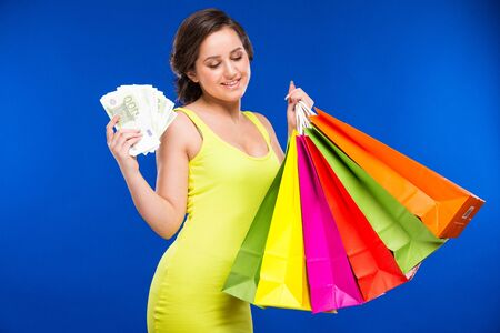 Young woman with money and shopping in retro dress